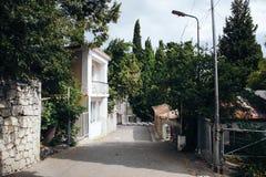 Die Straße der Stadt mit zweistöckigen Häusern und Bäumen Stockbild