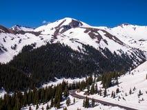 Die Straße, die durch Schnee kurvt, bedeckte Berge Lizenzfreies Stockfoto