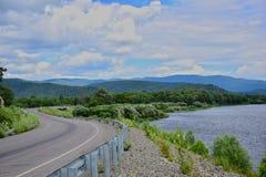 Die Straße entlang dem Fluss und den Bergen lizenzfreies stockbild