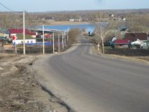 Die Straße führt zu das Dorf, das vom Berg sichtbar ist Die Blätter auf den Bäumen haben nicht noch wegen geblüht lizenzfreies stockbild