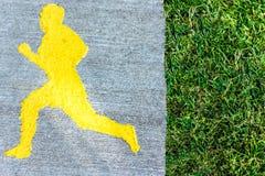 Die Straße für Sport mit dem Bild eines laufenden Mannes, nahe dem Gras stockfotografie