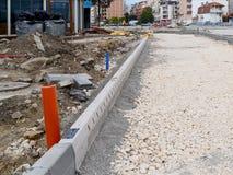 Die Straße im Bau in der Stadt: der Gehsteig ist bereits gelegt worden, wird der Kies gegossen und tamped, ist alles bereit stockbilder