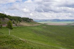 Die Straße läuft entlang den Fuß des Berges hinter dem grünen Tal, im Frühjahr lizenzfreies stockbild