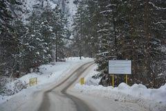 Die Straße mit Frost umgeben durch das Holz bedeckt mit Schnee Lizenzfreie Stockfotos