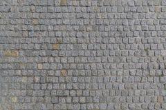 Die Straße wird mit Granitsteinen einer quadratischen Form als Hintergrund oder Hintergrund gepflastert Stockfoto