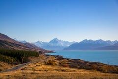 Die Straße zu den alpinen Dorf- und Gebirgswinden um den Rand von einem schönen blauen See lizenzfreie stockfotografie