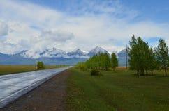 Die Straße zu den Bergen nach einem Regen Stockfotografie