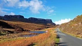 Die Straße zu Flodigarry nahe bei Lochan Nan Dunan mit dem Quiraing im Hintergrund Insel von Skye, Schottland stock footage