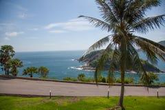Die Straße zum Hintergrund des Meeres und der Berge Stockfotografie