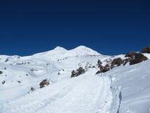 Die Straße, die zum snowcat geht und Touristen im Hintergrund des doppelköpfigen Elbruss nimmt lizenzfreies stockbild