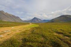 Die Straße zur Tundra in den subpolaren Urals mit Ansichten der Berge auf dem Horizont Lizenzfreie Stockfotografie