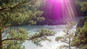 Die Strahlen der Sonne über dem Gebirgsfluss Lizenzfreies Stockfoto
