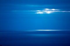 Die Strahlen der Sonne belichten die Meeresoberfläche und bilden einen hellen Fleck auf dem Wasser Lizenzfreie Stockfotografie