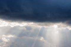Die Strahlen der Sonne hinter den Wolken Stockbild