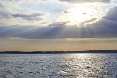 Die Strahlen der Sonne machen ihre Weise durch die Wolken auf dem riv Stockfotografie