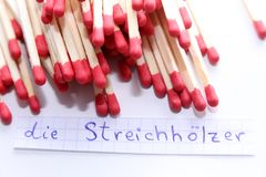 Die Streichhölzer, German word on a white note, matches on background. Learn new language, Die Streichhölzer, the German word for Matches written on a note stock image
