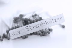 Die Streichhölzer, German word on a white note, matches on background. Learn new language, Die Streichhölzer, the German word for Matches written on a note royalty free stock image