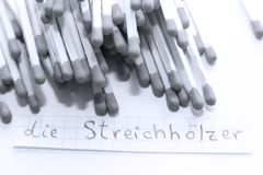 Die Streichhölzer, German word on a white note, matches on background. Learn new language, Die Streichhölzer, the German word for Matches written on a note stock photography