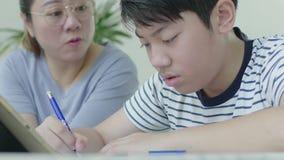 Die strenge asiatische Mutter überprüft die Ausbildung des Sohns stock video