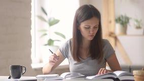 Die Studentin, die für Prüfung sich vorbereitet, las das Lehrbuch, das im Notizbuch merkt stock footage