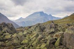 Die subpolaren Urals Bergspitze in den Wolken und in den Flusssteinen voran Stockfotografie