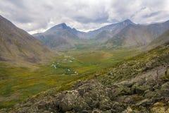 Die subpolaren Urals Bergspitze in den Wolken und in River Valley Stockfoto