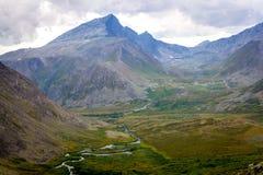 Die subpolaren Urals Bergspitze in den Wolken und in River Valley Lizenzfreie Stockfotos