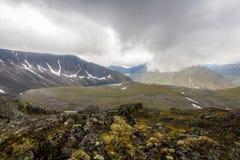Die subpolaren Urals Der See und das Feld zwischen Bergen unter Wolken Stockfotos