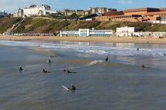 Die Surfer, die auf Bournemouth surfen, setzen Dorset England auf den Strand, das nahe zu Poole BRITISCH ist Lizenzfreies Stockbild