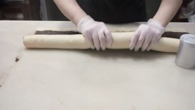 Die Szene: Der Koch wickelt Teig mit Zimt anf?llend in einer Rolle ein Produktion des Zimtgeb?cks Bild f?r Auslegung appetitanreg stock footage
