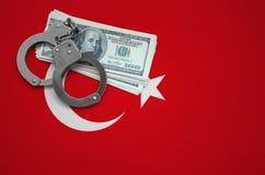 Die Türkei-Flagge mit den Handschellen und ein Bündel Dollar Das Konzept des Brechens des Gesetzes und der Diebverbrechen stockfotos
