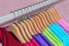 Die T-Shirts der mehrfarbigen Frauen, die an den hölzernen Aufhängern hängen Stockfotografie