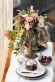 Die Tabelle wird mit einem schönen Blumenstrauß von Blumen verziert Lizenzfreie Stockbilder