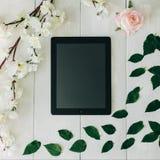 Die Tablette, die Rosarosenblume, die Grünblätter und die Kirschblüte verzweigen sich auf den weißen hölzernen Schreibtisch Trans Lizenzfreies Stockfoto
