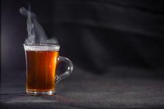 Die Tasse Tee auf einem dunklen Hintergrund lizenzfreie stockfotografie