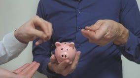 Die Teamwork mit zwei Geschäftsmännern macht Spareinlagen einsetzt Münzen in ein Sparschwein Sparschwein-Geschäftskonzept mit zwe stock video