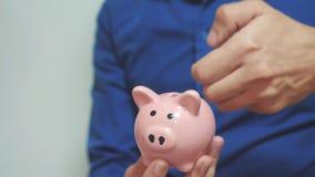 Die Teamwork mit zwei Geschäftsmännern macht Spareinlagen einsetzt Münzen in ein Sparschwein Sparschwein-Geschäftskonzept mit zwe stock footage
