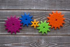 Die Teile eines Farbpuzzlespiels der Gänge werden in einen zusammengebaut auf hölzernem Beschaffenheitshintergrund lizenzfreies stockfoto