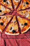 Die Teile Pizza mit Salami und Pilz dienten auf tableclothes auf einer hölzernen Küche Stockfoto