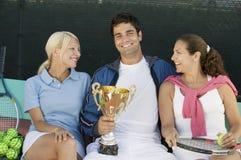 Die Tennisspieler, die am Tennisplatz sitzen, bemannen das Halten des Vorderansichtporträts der Trophäe stockfoto