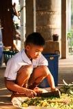 Die thailändischen Studenten, die auf dem Grundgebrauch ein Messer sitzen, hackten Gemüse für in der Schule kompostieren Stockbilder