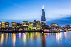 Die Themse-Damm und London-Skyline bei Sonnenuntergang Lizenzfreie Stockfotos