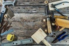 Die Tischlerwerkzeuge auf Holzbank, Fläche, Meißel, Holzhammer, Maßband, Hammer, Zangen, Zangen, Niveau, Nägeln und einer Säge lizenzfreie stockfotos