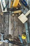 Die Tischlerwerkzeuge auf Holzbank, Fläche, Meißel, Holzhammer, Maßband, Hammer, Zangen, Zangen, Niveau, Nägeln und einer Säge Lizenzfreie Stockbilder