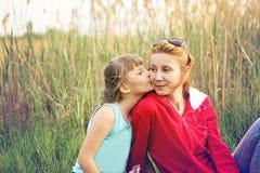 Die Tochter küsst ihre Lieblingsmutter auf der Backe Lizenzfreies Stockbild