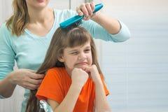 Die Tochter zerfrisst das Schauen im Spiegel, während Mutter ihr Haar kämmt Lizenzfreies Stockfoto