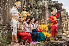 Die Touristen, die für Foto mit Männern und Frauen aufwerfen, kleideten in der traditionellen kambodschanischen Ausstattung in An lizenzfreies stockfoto