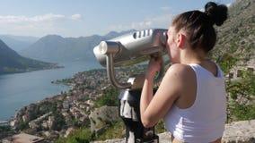 Die Touristenuhren durch Ferngläser von einer Höhe stock video