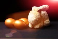 Die traditionellen Eier, die in der goldenen Farbe mit Kaninchen gemalt werden, spielen Stockbild