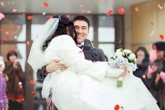 Die tragende Braut des Bräutigams in seinen Armen, die Menge wirft Blumenblätter und Reis Glückliche Hochzeit Stockfotografie